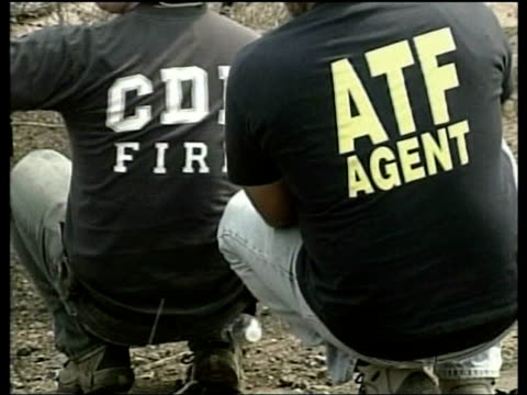 reward offered for capture of suspected arsonists VIA Irvine PAN from road to fire officers and ATF agents investigating area of burnt scrub land...