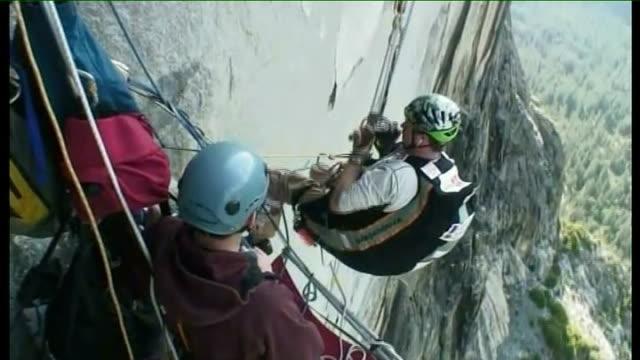 vidéos et rushes de yosemite national park: ext major phil packer scaling el capitan mountain using ropes and unfurling union jack flag - yosemite national park