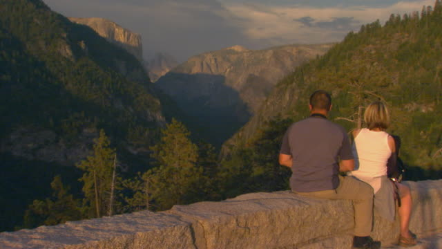 california, yosemitepeople sitting on stone wall overlooking mountain scenic view - stone wall stock videos and b-roll footage