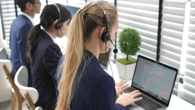 Call Center businesswoman and Team working with a headset for Support her Customer and accompanied by her team in call center