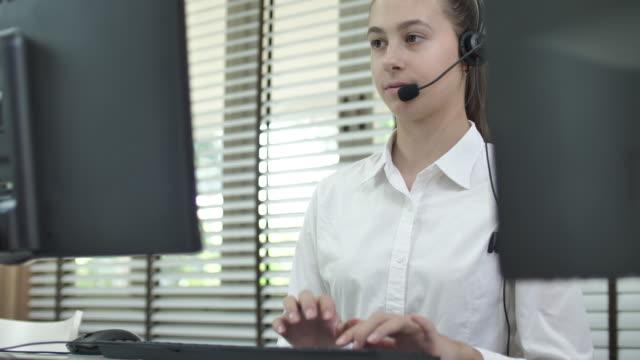 vidéos et rushes de opérateur de centre d'appel pendant un appel à la clientèle - une seule femme d'âge moyen