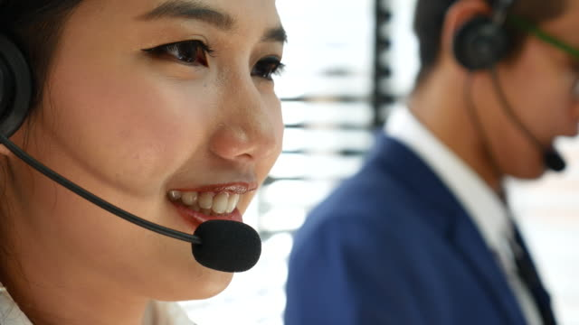 call center woman working in a call center using a headset - asia stock videos & royalty-free footage