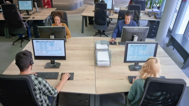 cs ld call centre operators answering calls at the workstations in a modern office - headset stock videos & royalty-free footage