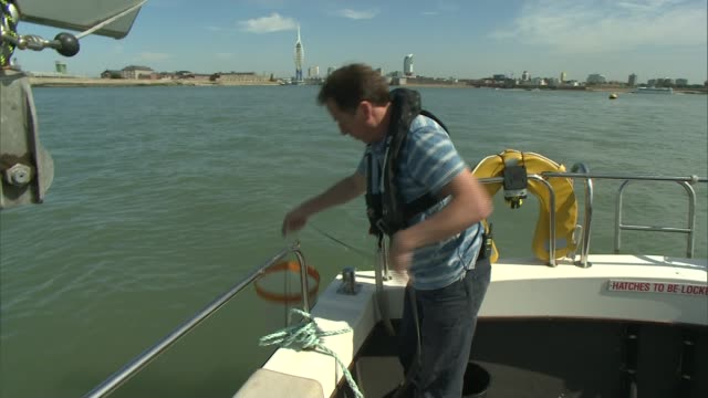 call for ban on microbeads in cosmetics due to fears of environmental damage in the oceans; england: solent coastline: int boat driver at controls... - herunterlassen stock-videos und b-roll-filmmaterial