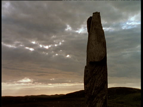 callanish stone in silhouette with vast grey clouds above, outer hebrides - hebrides stock videos and b-roll footage