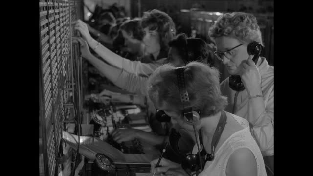 montage a caller dialing a rotary phone to report a disturbance, switchboard workers connecting the caller to the british police, and officers alerting the patrolman on duty / united kingdom 1950's - rotary phone stock videos and b-roll footage