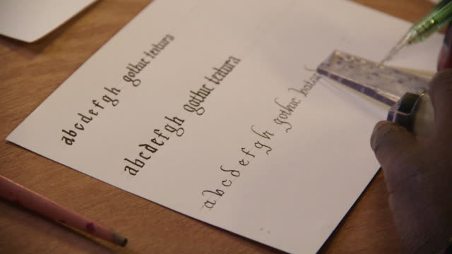 a calligrapher uses a ruler and mechanical pencil to mark lines under three styles of gothic handwriting, uk. - kalligraphieren stock-videos und b-roll-filmmaterial
