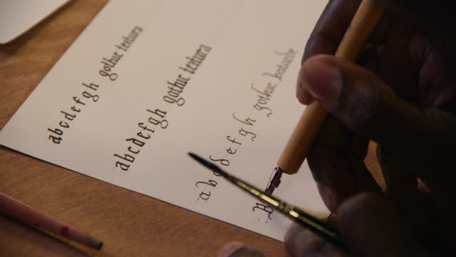 a calligrapher writes 'blackletter' between scored lines on a piece of paper, uk. - english language stock videos and b-roll footage