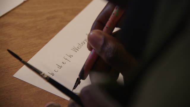 A calligrapher writes the letters A to H in French cursive, UK.