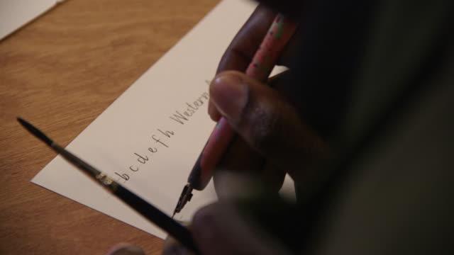 vídeos y material grabado en eventos de stock de a calligrapher writes the letters a to h in french cursive, uk. - escribir