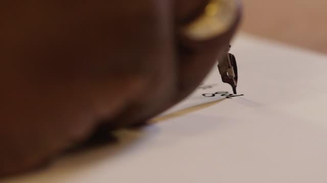 vidéos et rushes de a calligrapher writes the words 'gothic textura', uk. - stylo