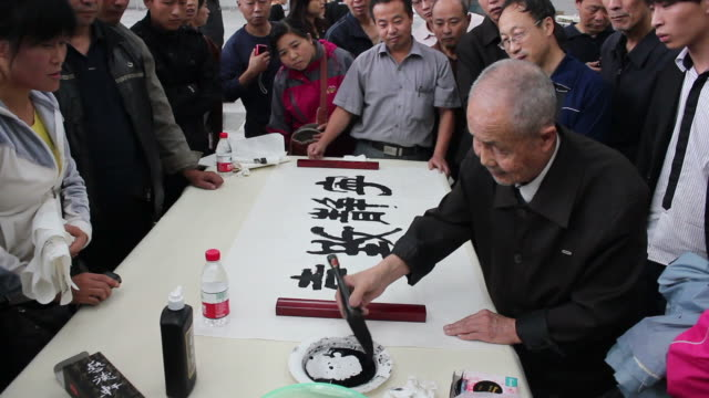 ws calligrapher writing chinese calligraphy in black ink on rice paper/xian,shaanxi,china - washi paper stock videos & royalty-free footage