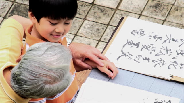 calligraphy grandfather and grandson writing - washi paper stock videos & royalty-free footage