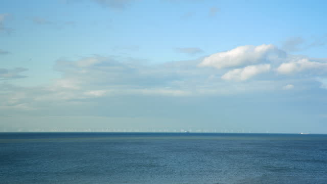 """calm blue sea with wind farm in distance, uk - """"bbc universal"""" stock videos & royalty-free footage"""