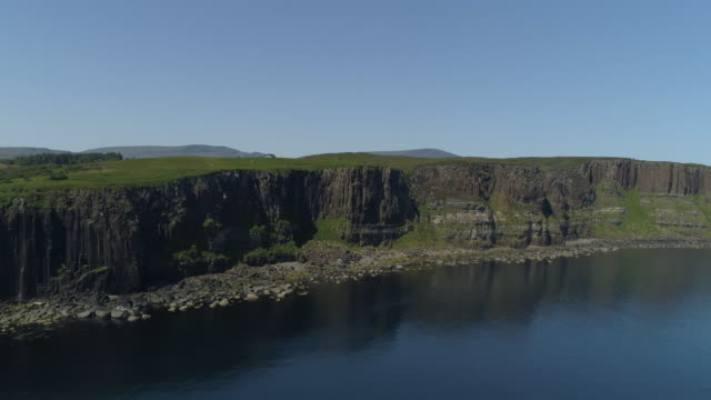 calm countryside scene of coastal cliffs covered in lush green grass and the dark blue sea below - hebrides stock videos & royalty-free footage