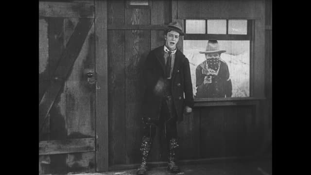 1922 calm man (buster keaton) robs casino until his cardboard companion is found out and he is thrown out - bankräuber stock-videos und b-roll-filmmaterial
