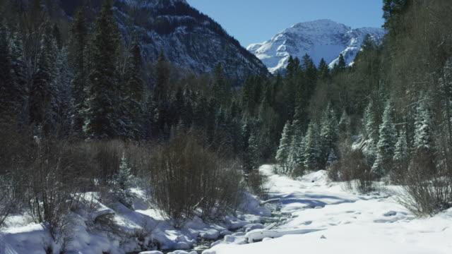 明るい、澄んだ青い空の下でユーレイ、コロラド州の近くの背景に冬のサンファン山脈、ロッキー山脈の雪に覆われたピークで森に囲まれた雪に覆われた渓谷をのんびりした山ストリーム フ - ユアレイ市点の映像素材/bロール