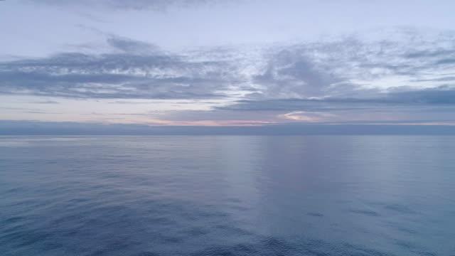 Calm ocean aerial at dusk, forward move