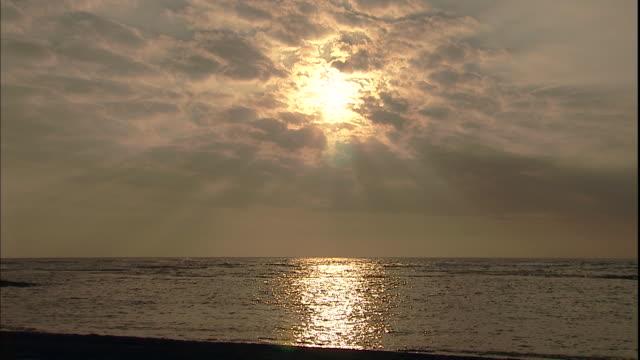 Calm ocean water reflects the sun shining through clouds.