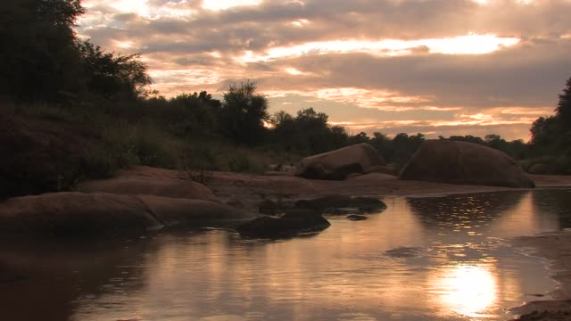 a calm river reflects a dramatic sky. available in hd. - desert oasis stock videos & royalty-free footage
