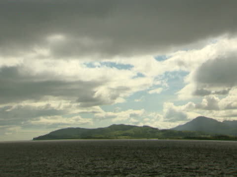 vidéos et rushes de calm sea, cliffs in background, calm sea, cloudy, tranquil, natural, relaxing - mull