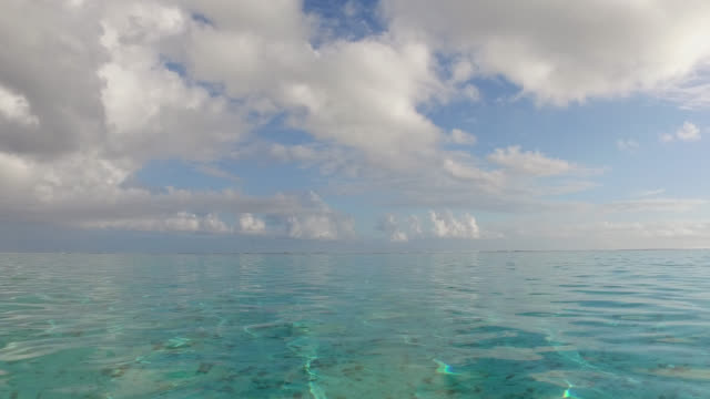 calm sea with blue sky with clouds - huahine island stock videos and b-roll footage