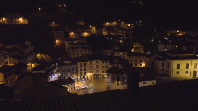 4K | Calm small fishing village at night seen from high angle view. Yellow lamps light some group of people in the downcenter square in a warm night at Cudillero.