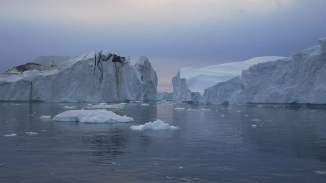 calm view of icebergs floating in disko bay during sunset - inlet stock videos & royalty-free footage