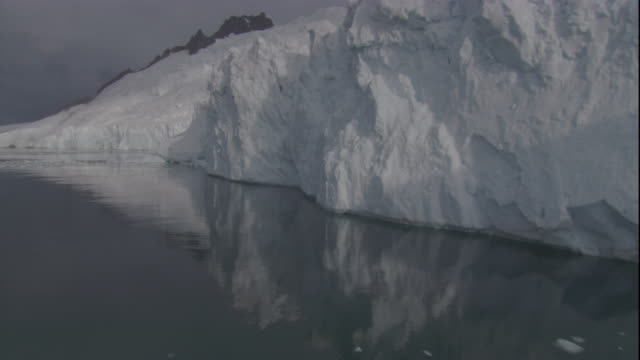 calm water reflects an ice shelf in antarctica. - antarctic ocean stock videos and b-roll footage