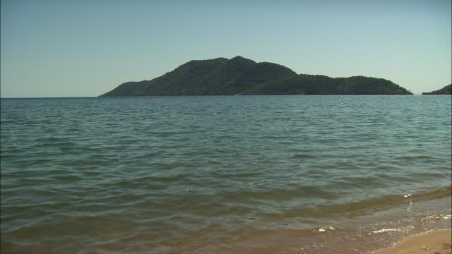 vídeos de stock e filmes b-roll de calm waters lap onto the shoreline of lake malawi. - malávi