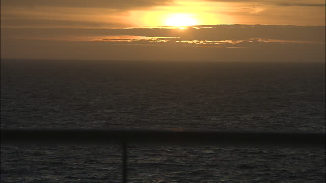 Calm waves move past a ship's railing as the golden sun glows from behind clouds.