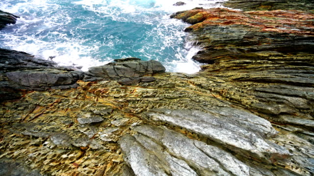 calm waves splash on rocky shore - rock formation stock videos & royalty-free footage