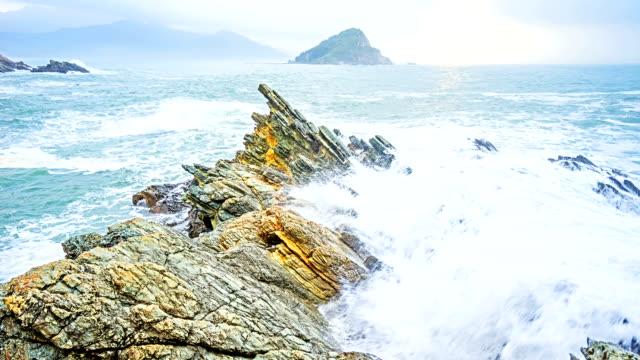 Calm waves splash on rocky shore