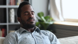Calm young african man meditate on sofa with eyes closed