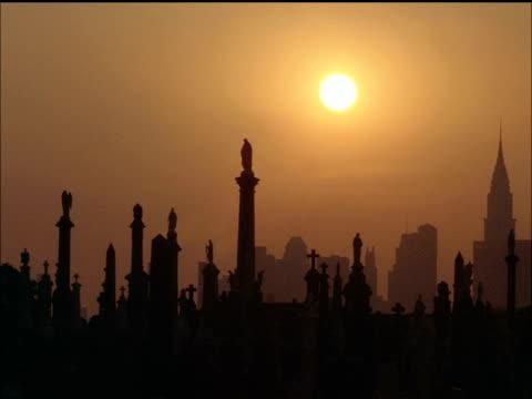 vídeos de stock e filmes b-roll de calvary cemetary and ny skyline at dusk - nevoeiro fotoquímico