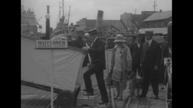 calvin and grace coolidge decar on dock with the president holding pet dog paul pry on a leash they walk up gangplank to the yacht mayflower as... - präsident stock-videos und b-roll-filmmaterial