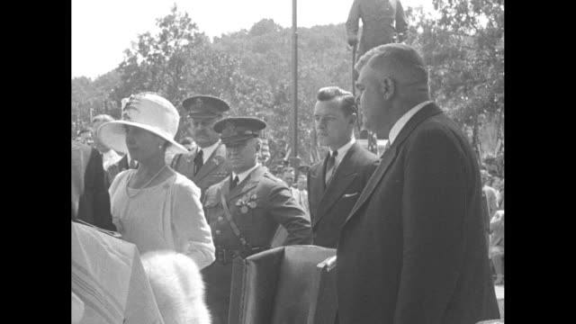 Calvin and Grace Coolidge sitting in chairs outside / A crowd of thousands with men in uniform in foreground / VS the Coolidges stand Calvin steps to...
