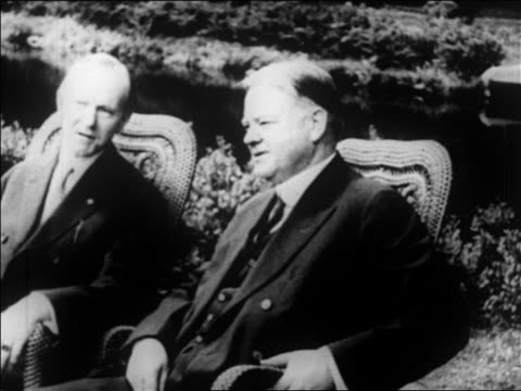 vídeos y material grabado en eventos de stock de calvin coolidge + herbert hoover sitting outdoors on lawn chairs + talking / newsreel - 1928