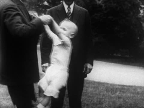 Calvin Coolidge playing with child star Baby Snookums / Senator Reed Smoot in background / newsreel