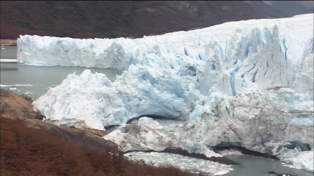 calving ice falls off glaciar perito moreno and splashes into water, patagonia - patagonia chile stock videos and b-roll footage