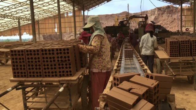 cambodia's brick making factories are luring labourers by assuming crippling debts in exchange for long hours and low wages in a system that rights... - the machine: master or slave stock videos & royalty-free footage
