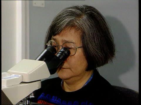 Cambridge Addenbrookes Seq Lab technicians looking thru microscopes at smear test samples