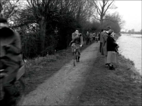 Cambridge Boy in tree watching race / GV Rowing boats coming towards on river / MS Cyclists towards and past on towpath / MS Two boats nearing each...
