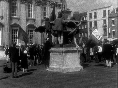 Cambridge Students march Students stand around Students on statue Student sets fire to academic gowns Custodian hoses students they run in to stop him