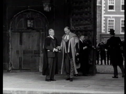 dog is honorary cat; lib b/w rab butler thru door in college gown b/w butler and others along in procession - cambridge university stock videos & royalty-free footage