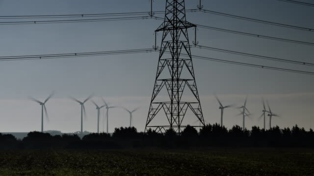 cambridgeshire countryside with silhouetted electricity pylon in the foreground and 12 wind turbines in the distance - hochspannungsmast stock-videos und b-roll-filmmaterial