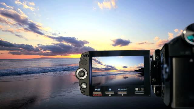 vídeos de stock e filmes b-roll de gravação de vídeo completa na praia ao pôr do sol - câmara fotográfica