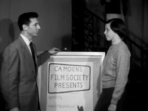 MS 'Camden's Film Society Presents' sign VS People walking down stairs into theater lobby President Al Sindler SOT talking w/ Mrs Joseph Busken about...