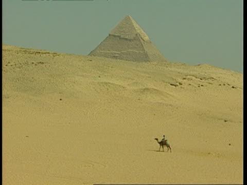 vídeos y material grabado en eventos de stock de wa camel being ridden through desert, pyramid on horizon, egypt - desgastado por el tiempo