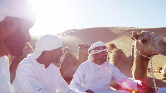 vídeos de stock, filmes e b-roll de camel caravan train travelling in middle eastern desert - adereço de cabeça